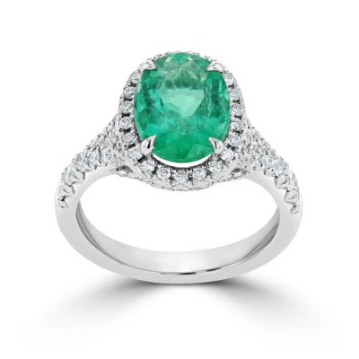 A deep green emerald with a halo setting.