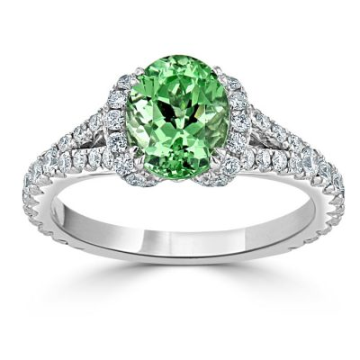 A green garnet stone surrounded by small diamonds set into a platinum ring.