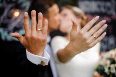 Blurred figures of happy and smiling bridegroom and bride kissing and showing wedding rings on their fingers