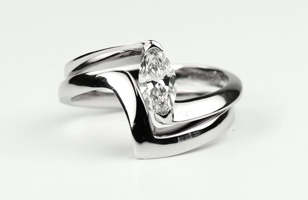 marquise diamond engagement ring with interlocking shaped wedding ring