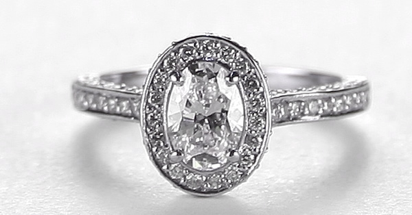oval diamond engagement ring with surrounding an shoulder set round brilliant cut diamonds