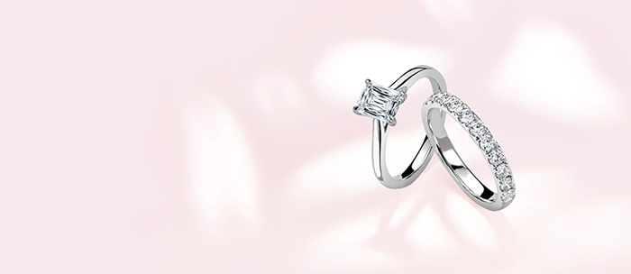 Two styles of engagement rings set in white gold on a pink gradient background